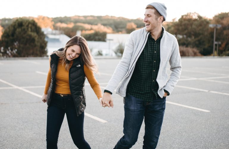 A couple is holding hands and laughing