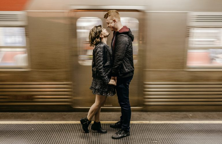 A couple is atnding at the metro and holding hands