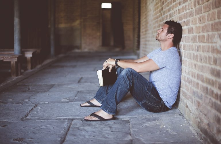 a thinking man sitting on the floor